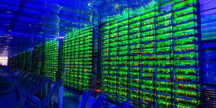 Illuminated mining rigs operate inside racks at the CryptoUniverse cryptocurrency mining farm in Nadvoitsy, Russia, on Thursday, March 18, 2021. The rise of Bitcoin and other cryptocurrencies has prompted the greatest push yet among central banks to develop their own digital currencies. Photographer: Andrey Rudakov/Bloomberg via Getty Images