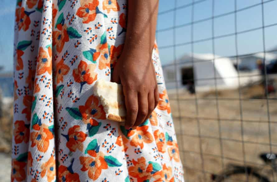 A child clutches some bread outside a camp for migrants and refugees on the Greek island of Lesbos.
