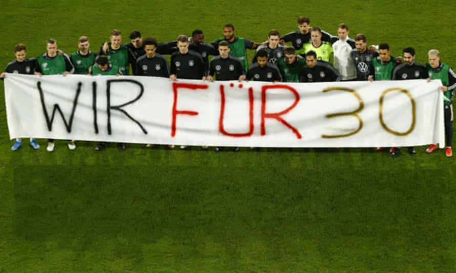 """Germany's squad poses with a """"We Support 30"""" banner, in reference to the UN's list of 30 human rights, before the game."""