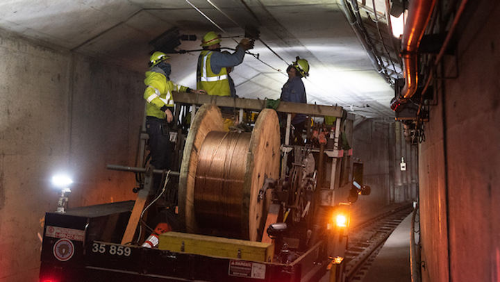 SFMTA crew installing new overhead wire in the subway tunnel.