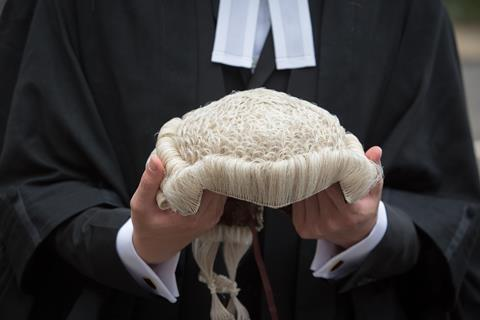 An anonymous barrister holds their wig in front of them