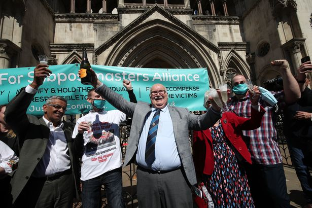 Former post office worker Tom Hedges (centre) holds up a bottle and glass of champagne in celebration outside the Royal Courts of Justice, London, after having his conviction overturned by the Court of Appeal