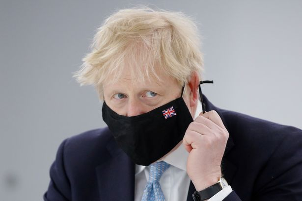 Britain's Prime Minister Boris Johnson adjusts his mask during a visit to Severn Trent Academy in Coventry, West Midlands, Britain, May 7, 2021