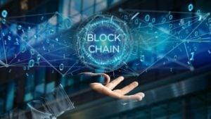 futuristic image of a hand with the words block chain floating above it. representing riot blockchain stocks