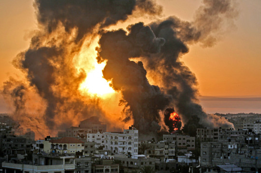 A fire rages at sunrise in Khan Yunish following an Israeli airstrike on targets in the southern Gaza strip, early on May 12, 2021. (AFP via Getty)