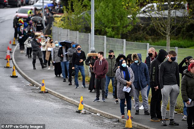 Members of the public are pictured queuing outside a vaccination centre in Bolton this morning as the local authorities rush to get jabs to as many people as possible