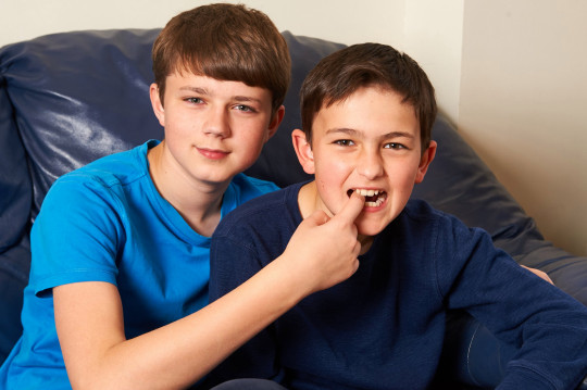 Harry (13) and Charlie (11) Davies-Carr celebrate 10 years of the viral video, Charlie bit my finger (Credits: Caters News Agency)
