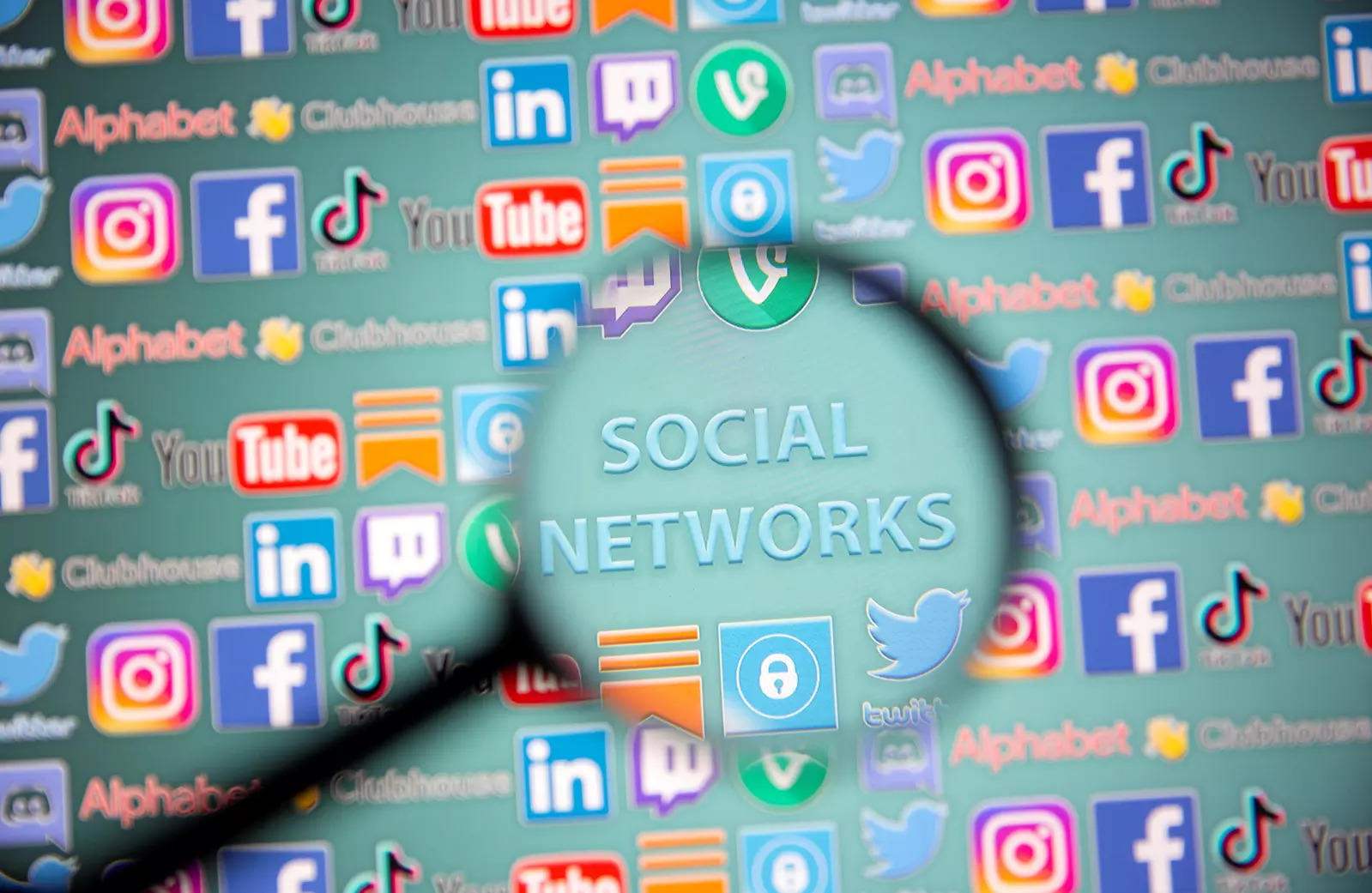 Social network words and social media logos are seen through magnifier displayed in this illustration taken