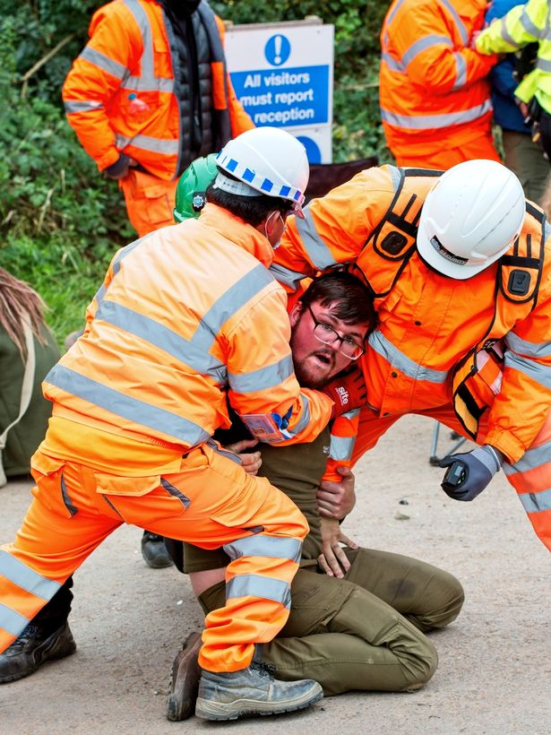Workmen remove one green protester at Cubbington Woods, one site for the line