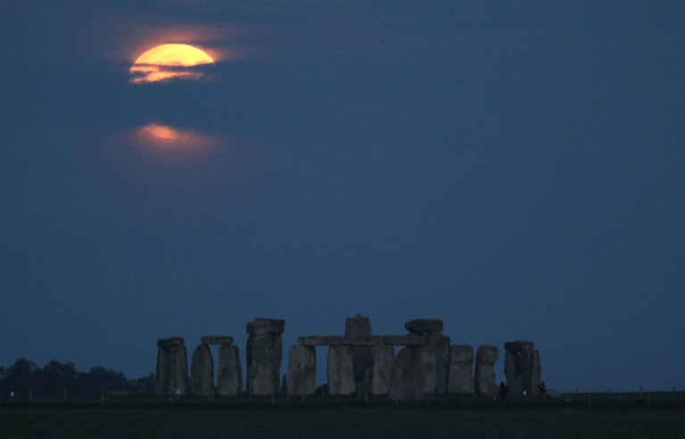 The Flower Moon partially blocked by clouds over Stonehenge in Wiltshire. (Credits: PA)