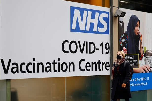 A pedestrian walks past an NHS Covid-19 vaccination centre in Westfield Stratford City