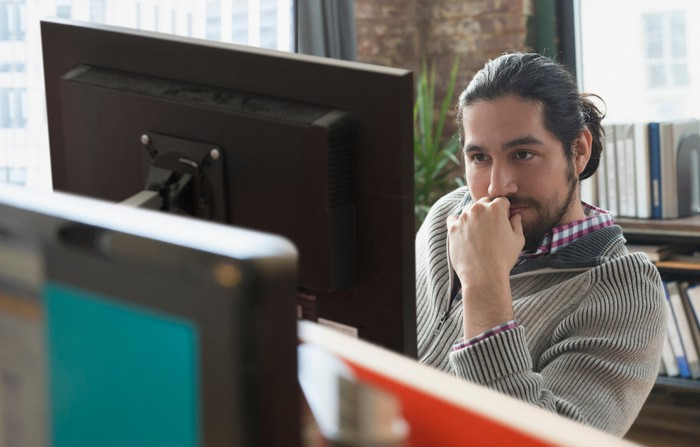 Man staring at computer screen as if concentrating deeply