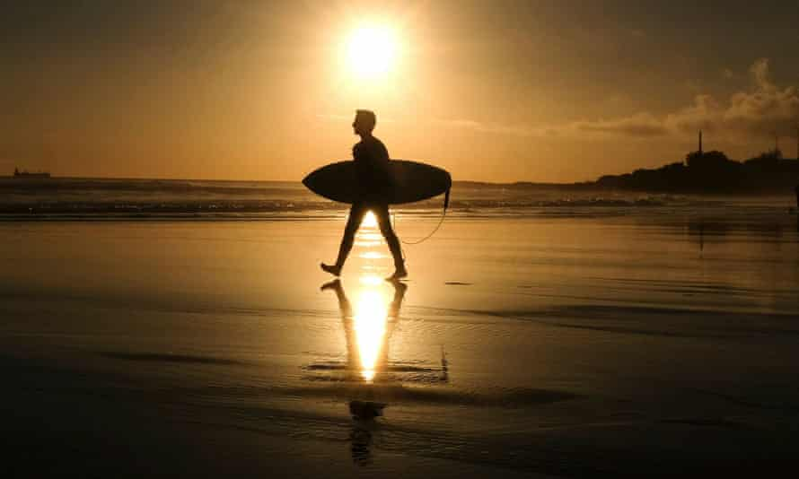 A surfer goes to the water at Carcavelos beach in Portugal.