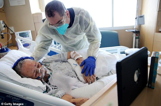 Patients are facing 'the financial version of long-haul COVID' - massive medical bills for COVID treatment. Pictured: Chaplain Kevin Deegan prays with COVID-19 patient Esperanza Salazar, as she speaks with family members remotely in Los Angeles, February 2021