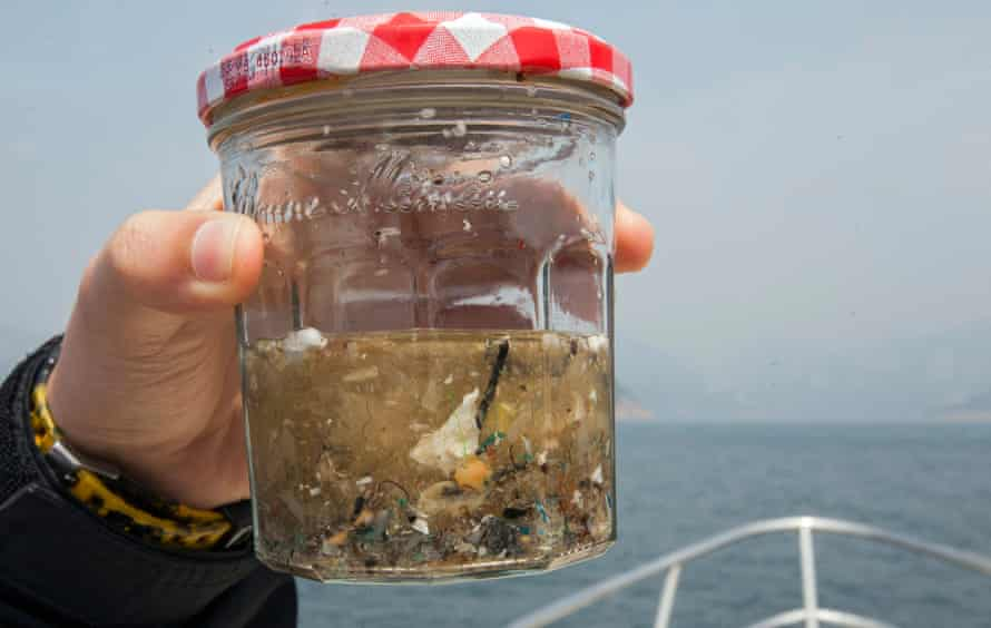An environmental sciences student from the University of Hong Kong holds up a glass jar containing a sample of microplastics collected from the ocean.