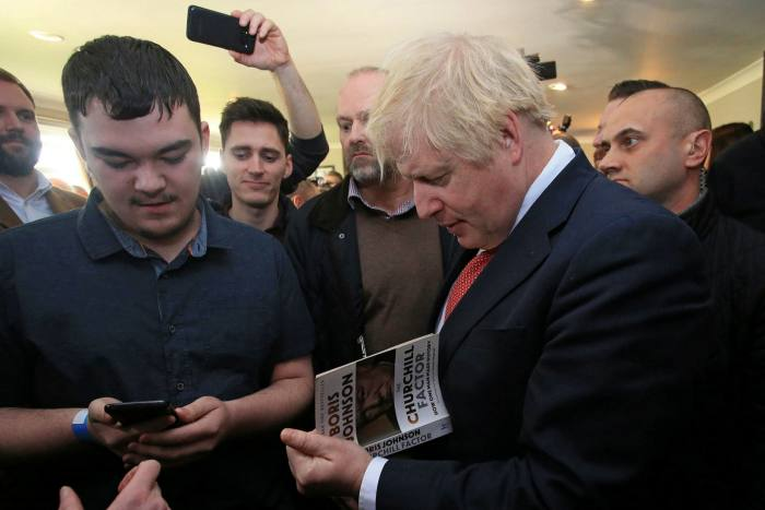 Boris Johnson signs a copy of one of his books in 2019