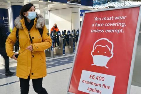 A commuter wearing a face mask walks past a sign at London Waterloo train station reminding the public they can be fined for not wearing one