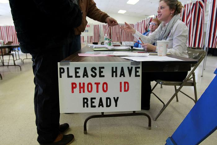 A man hands over ID at a polling station in New Hampshire, US