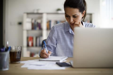 A woman writes in a notepad as she sits in front on a laptop