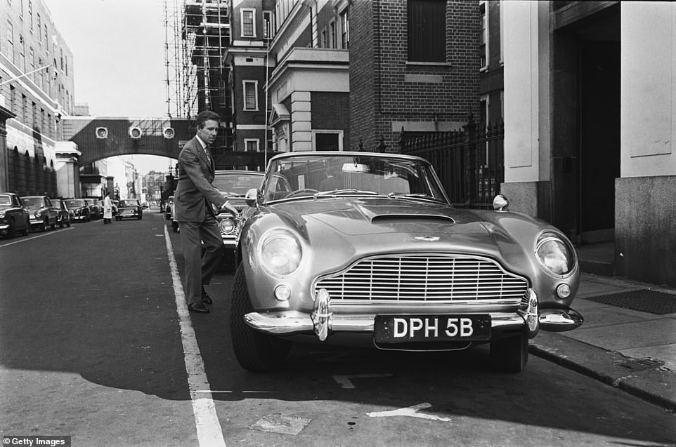 Anthony Armstrong-Jones, Lord Snowdon (1930-2017) opens the door of his Aston Martin DB5 coupe car parked on a street in London, 2nd July 1965
