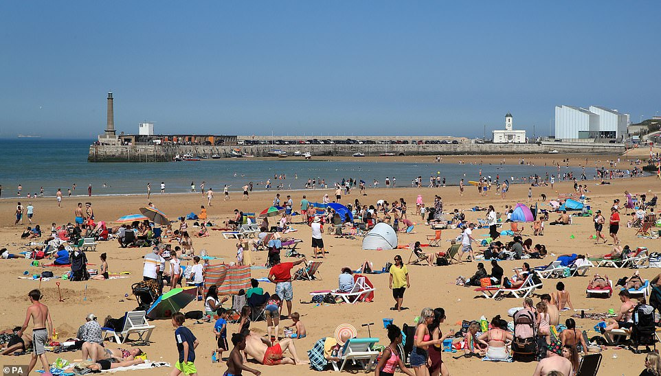 People are pictured enjoying the sunshine in Margate, Kent, today on what could be the warmest day of the year so far with temperatures stretching towards 77F (25C) across the country