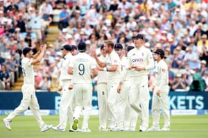 Stuart Broad celebrates with teammates after taking the wicket of Tom Latham.
