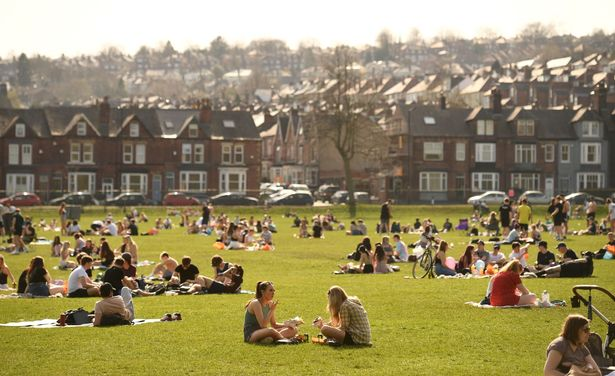 People enjoy the sunshine in the park - with indoor gatherings of more than six people banned (file photo)