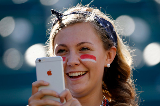 A fan of the United States takes a picture with her IPhone