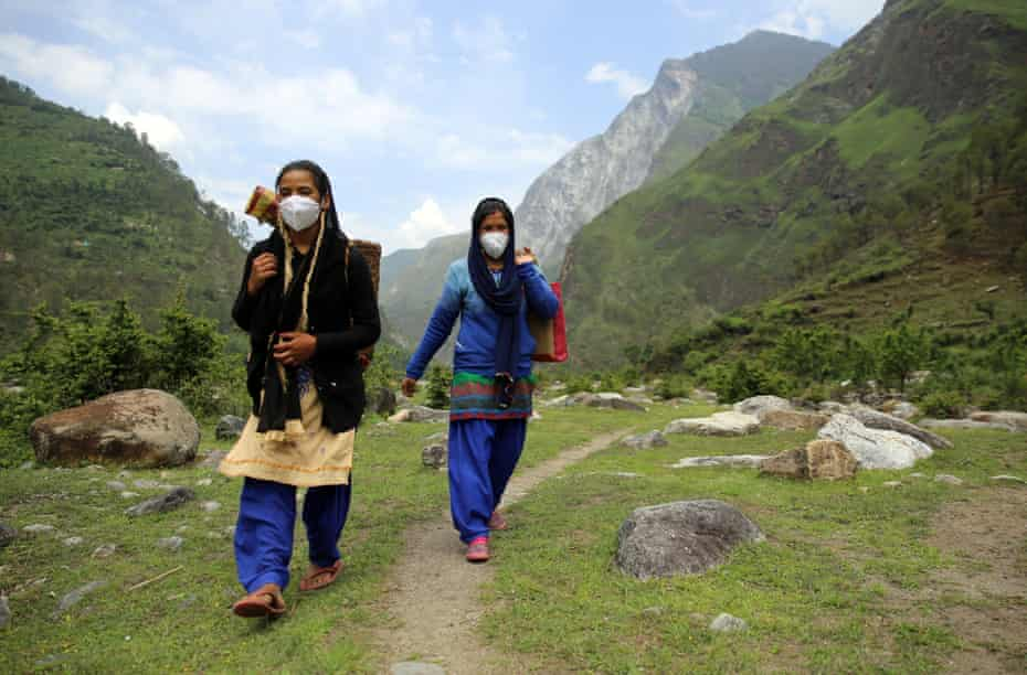 Godavari Devi, right, a community health worker, crosses the valley to provide hygiene kits and free rations to new mothers in Durmi.