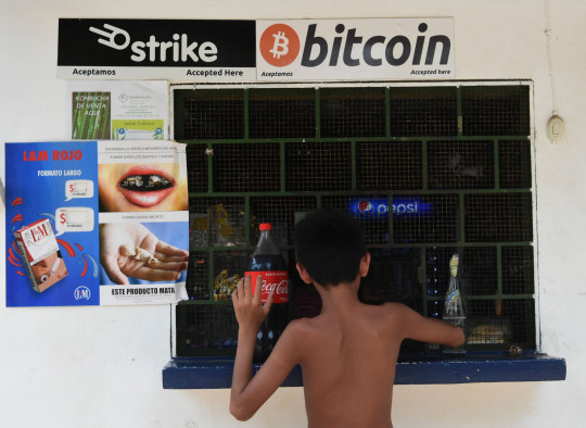 A man buys in a store that accepts bitcoins in El zonte, 56 km Suth east from San Salvador, on June 09, 2021. - Bitcoin is to become legal tender in El Salvador, the country's president said, making it the first nation to adopt a cryptocurrency for everyday use. Lawmakers in the Central American nation's Congress passed a bill late Tuesday that will eventually allow the famously volatile digital currency to be used for many aspects of daily life, from property purchases to tax contributions. (Photo by Stanley ESTRADA / AFP) (Photo by STANLEY ESTRADA/AFP via Getty Images)