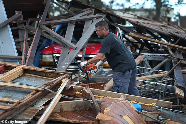 The NOAA has predicted an above-average number of hurricanes for the 2021 season. Pictured: A homeowner in Lake Charles, Louisiana, tries to free his truck from debris caused by Hurricane Laura in August 2020