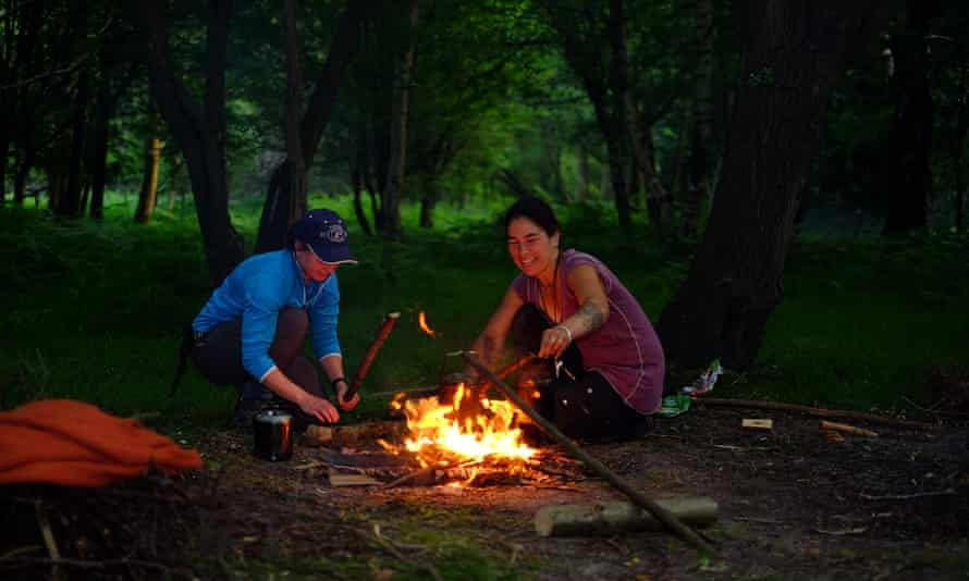couple with campfire in woods