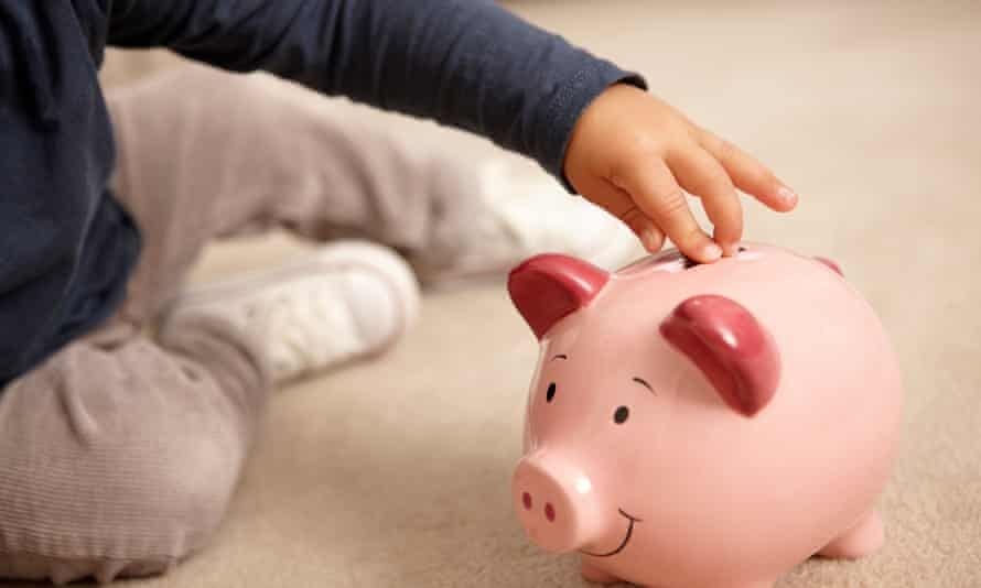 Close up of boy putting coins in piggy bank