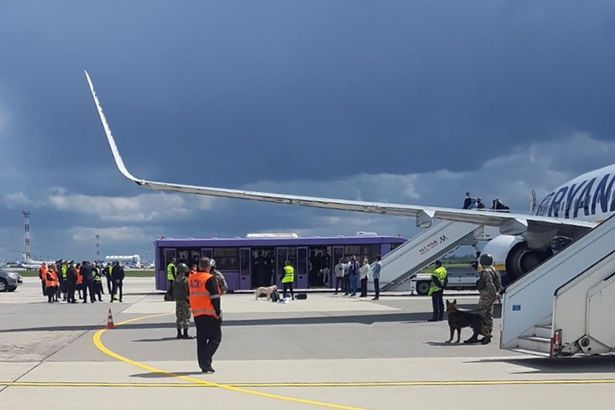 Airport personnel and security forces are seen on the tarmac in front of a Ryanair flight which was forced to land in Minsk, Belarus, May 23, 2021