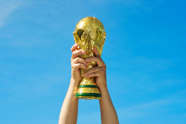 A pair of hands lifting the FIFA World Cup trophy against a clear blue sky.