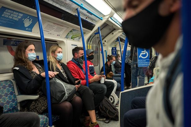Commuters wearing face masks or covering due to the COVID-19 pandemic, sit aboard a Victoria Line London underground tube train as they travel during the evening 'rush hour' in central London on September 23, 2020