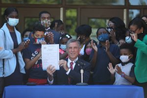 Governor Carney holds up House Bill 198 surrounded by students, legislators and advocates