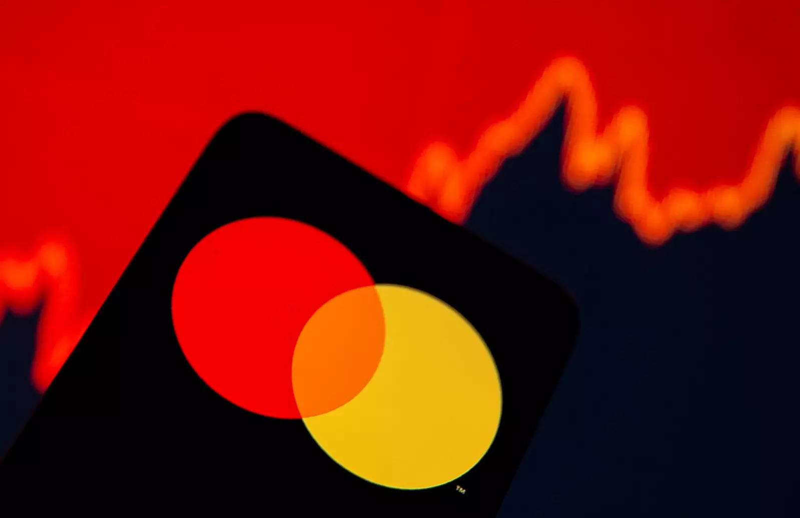 Smartphone with Mastercard logo is seen in front of displayed stock graph in this illustration