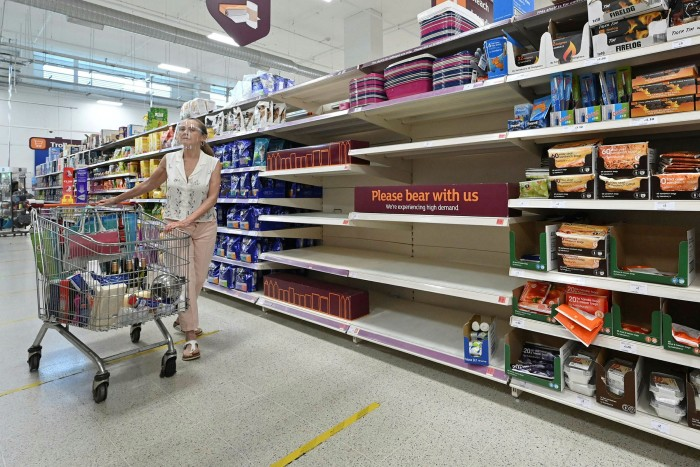 A shopper walks past a sign advising that products are temporarily out of stock