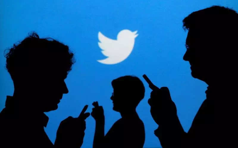 FILE PHOTO: People holding mobile phones are silhouetted against a backdrop projected with the Twitter logo in Warsaw
