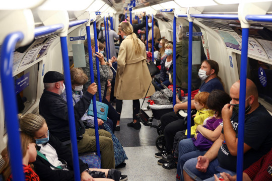 People wearing protective face masks commute aboard a train on the London Underground, amid the coronavirus disease (COVID-19) outbreak