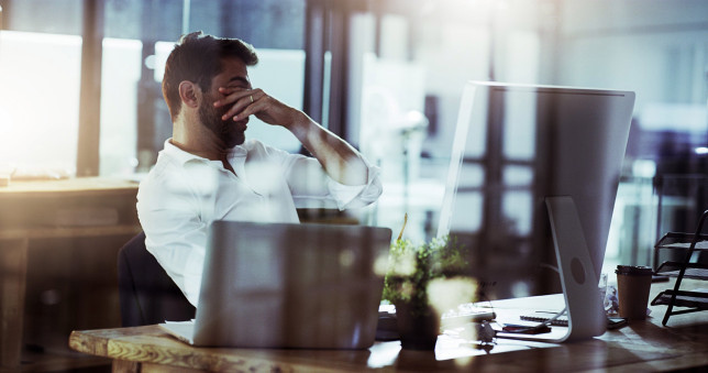 Cropped shot of a young businessman looking stressed while working late in the office