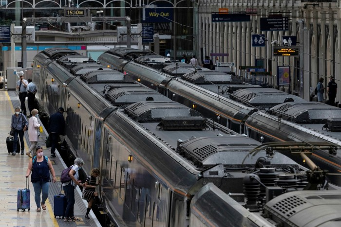 Commuters board a train at Paddington Station in London