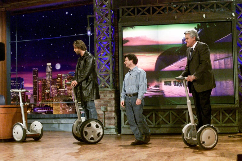Russell Crowe and Jay Leno ride Segways as Dean Kamen watches.