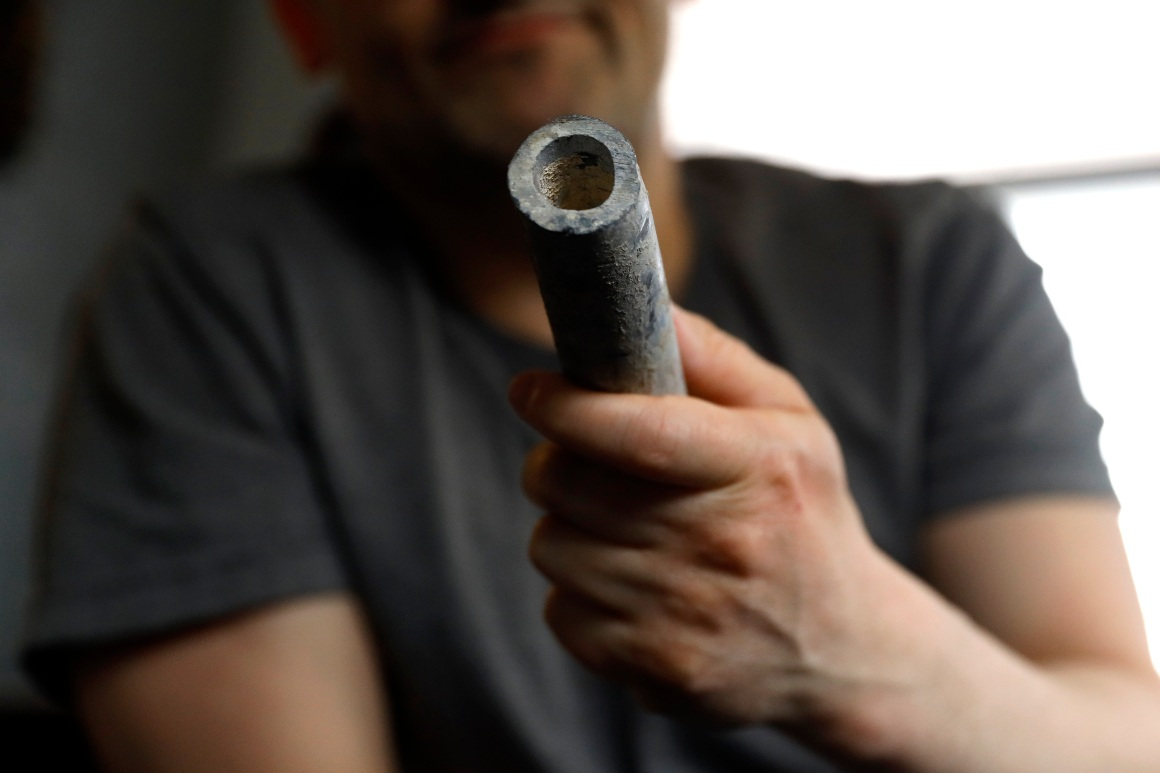 An environmental justice activist shows a piece of lead pipe obtained from his residence during his home renovation.