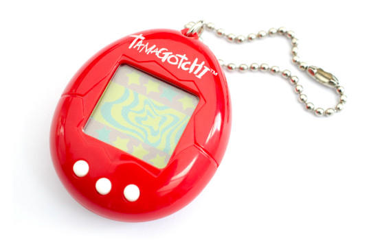 A red Tamagotchi is photographed in a studio in front of a white background.