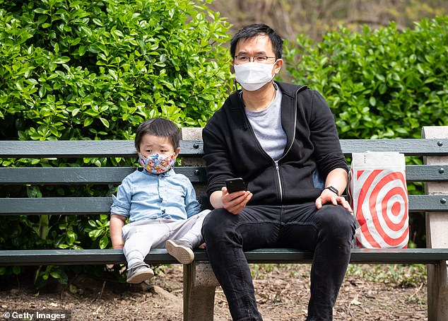 The CDC only recommends wearing a mask at home if a person is ill with the virus or if someone is in the same room as the sick person providing care. Pictured:A child and an adult wear masks as they sit on a bench in Central Park in New York City, April 2021