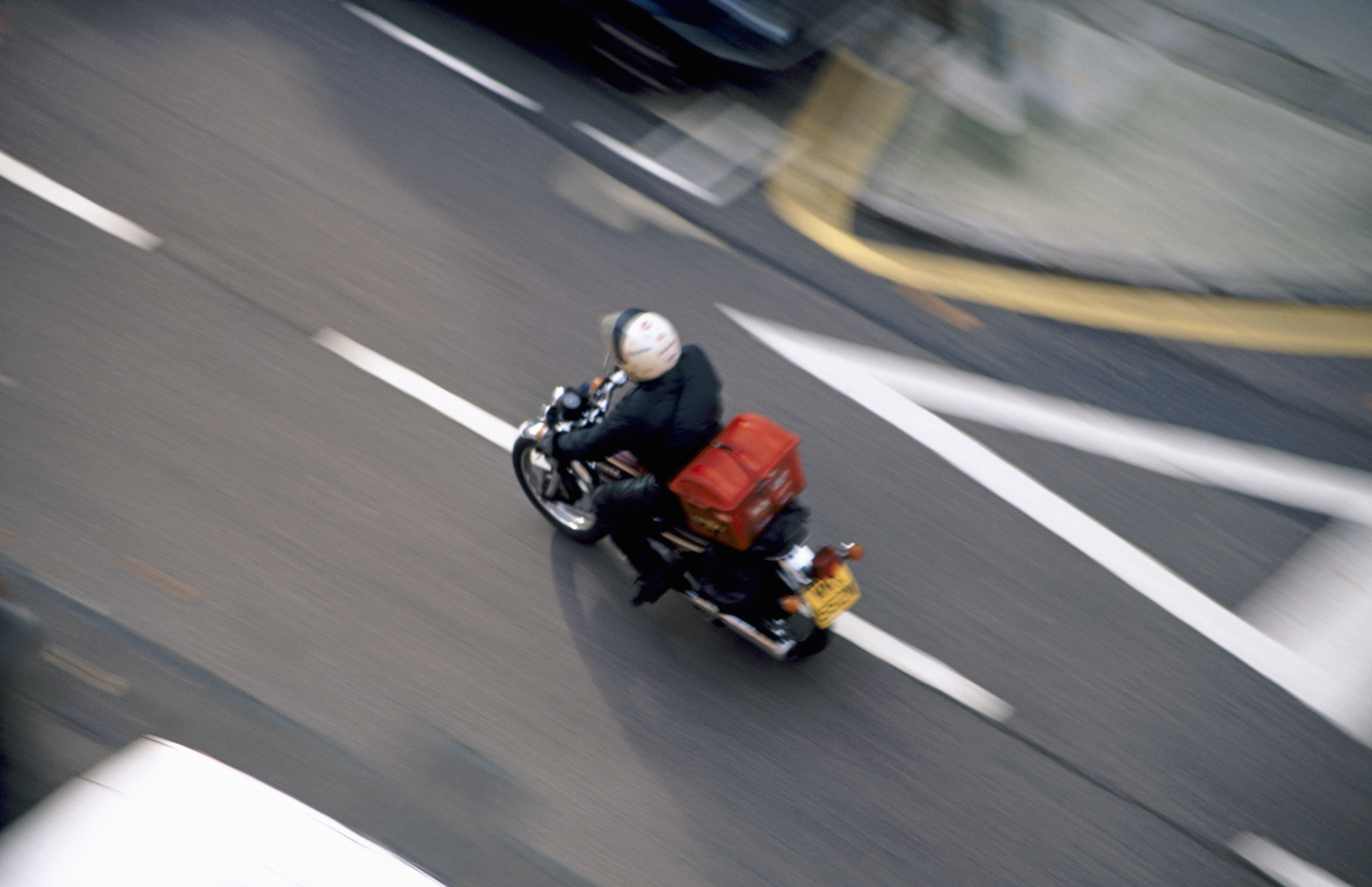 Image of a motorcycle courier speeding down a street.