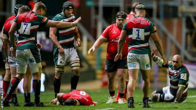 John Cooney of Ulster lies injured after being caught by Nemani Nadolo of Leicester Tigers, right, before leaving the pitch for a HIA during the Heineken Challenge Cup semi-final match between Leicester Tigers and Ulster at Welford Road