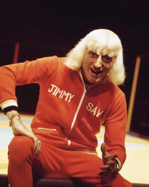 Jimmy Savile presenting the BBC chart show Top Of The Pops, circa 1973, wearing a personalised tracksuit.